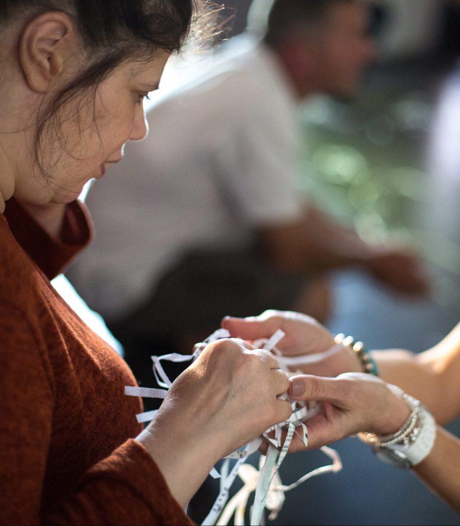 two women touch feeling shredded paper