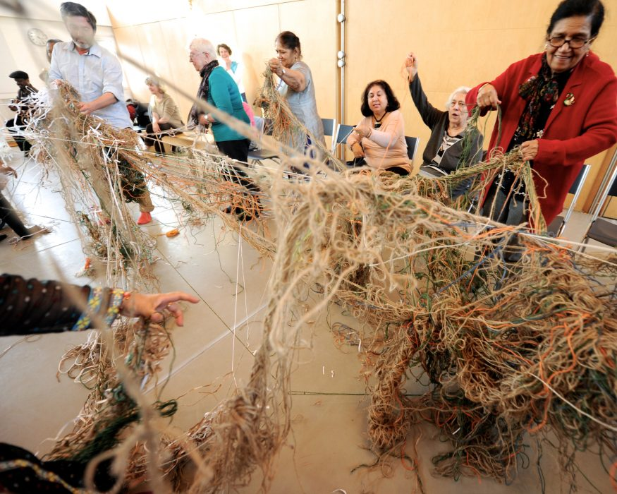 many people with a spiderweb of wool