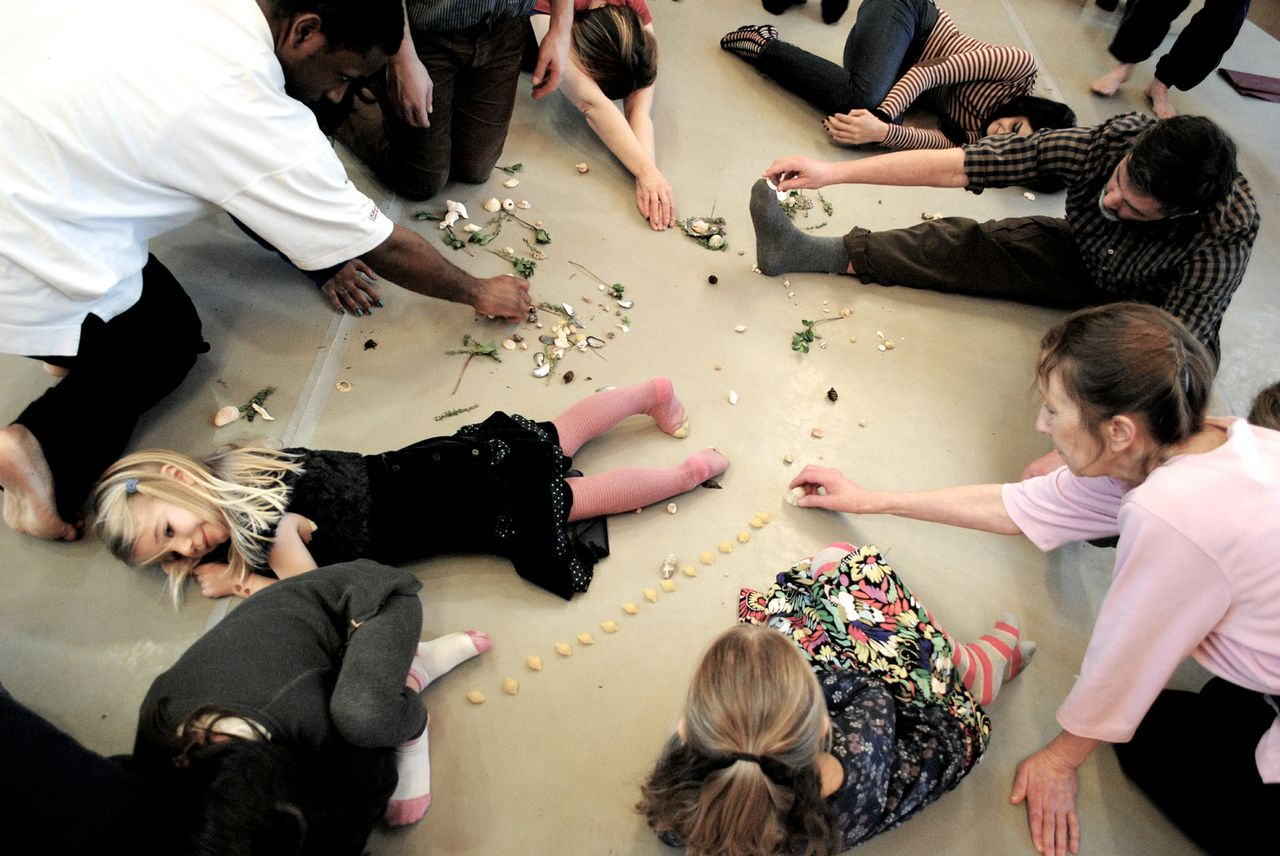 children and adults on the floor playing with pasta shapes and shells