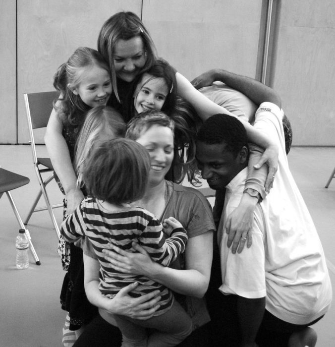 young children in a group hug smiling