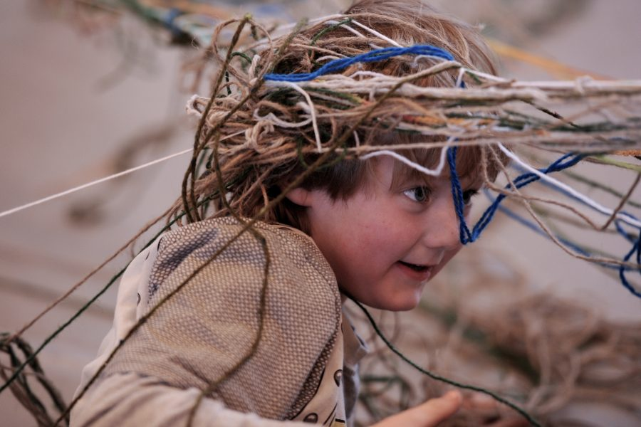 Young boy with woolen threads around his head