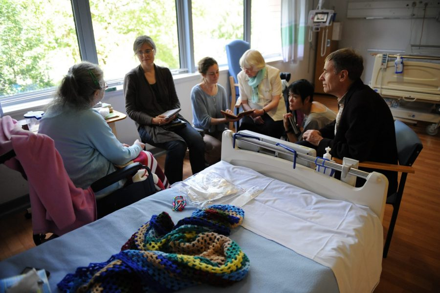 Artists and volunteers collaborate with artist patients around a hospital bed