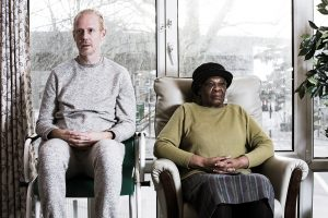 man and woman sitting facing camera