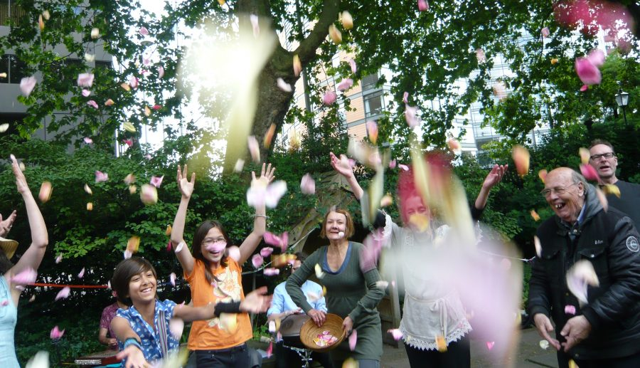 people in a garden jumping up throwing confetti