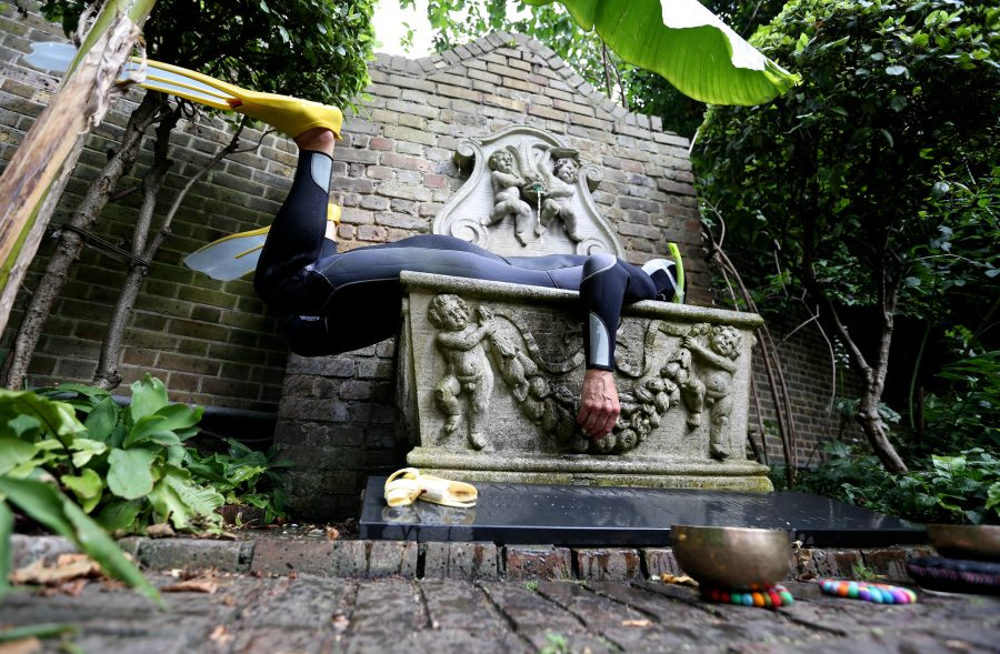 artist lying on a concrete sculpture in a garden