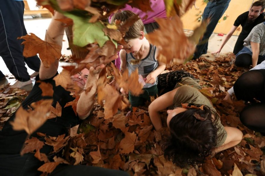young children playing in dry leaves