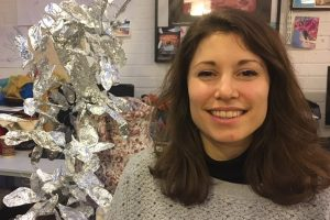 portrait of sarah smiling with silver sculpture
