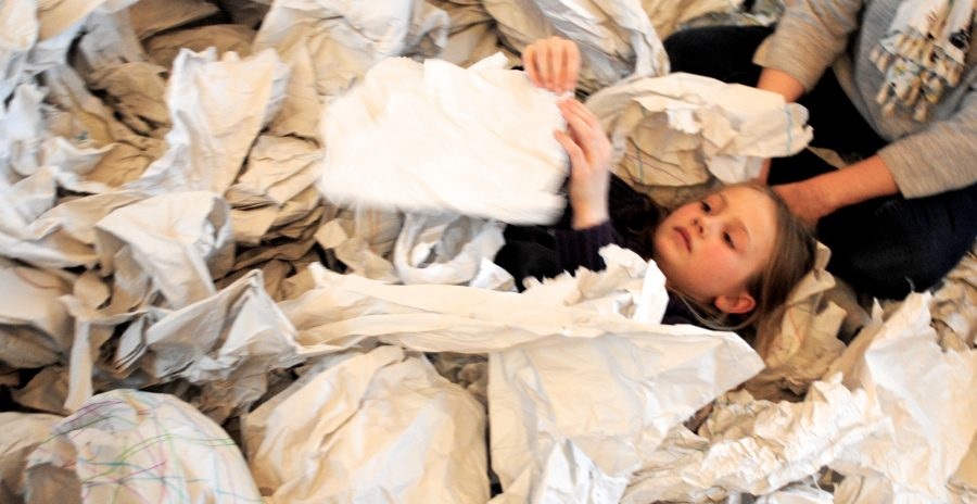 Child wrapped in sheet exploring sculpture
