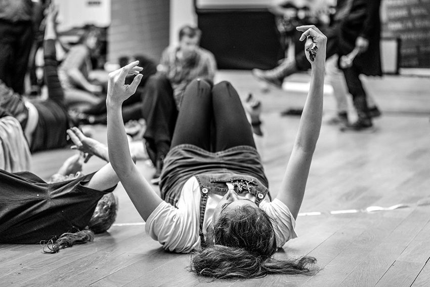 artist lying on the floor arms outstreatched