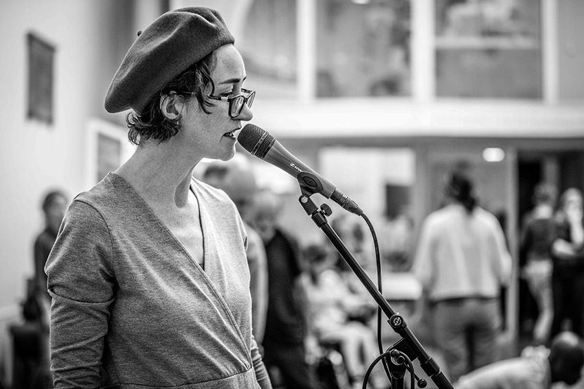 artist speaking into microphone wearing beret