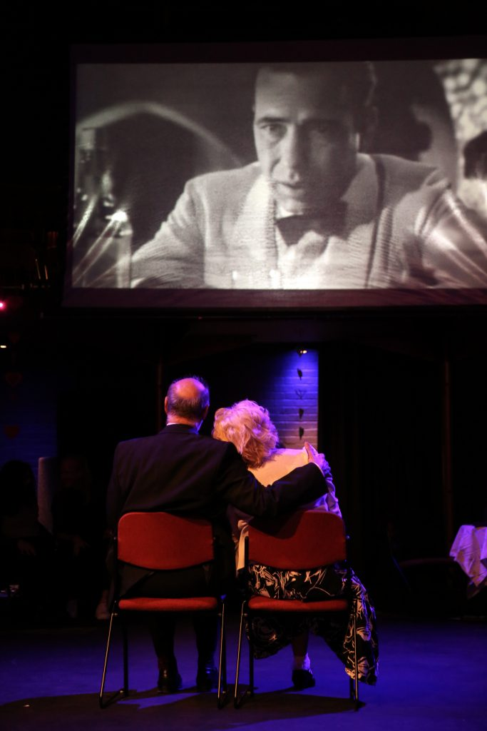 Two elderly people watching a movie