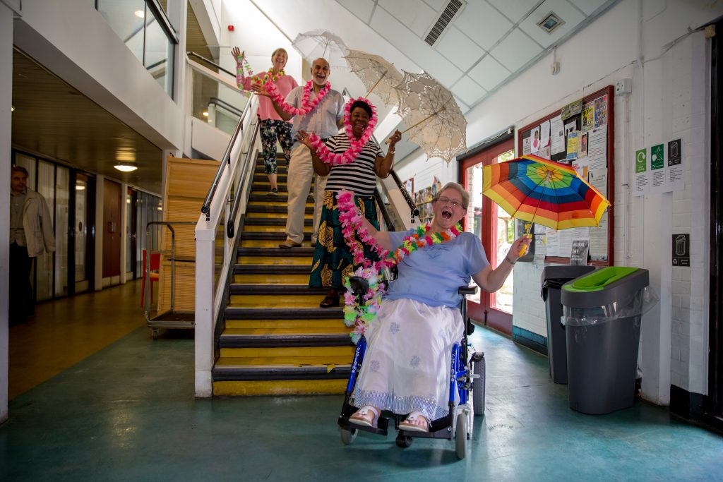 women with umbrellas and feather boas laughing on the stairs