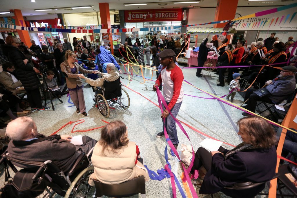 Many people in shopping centre with streamers around them