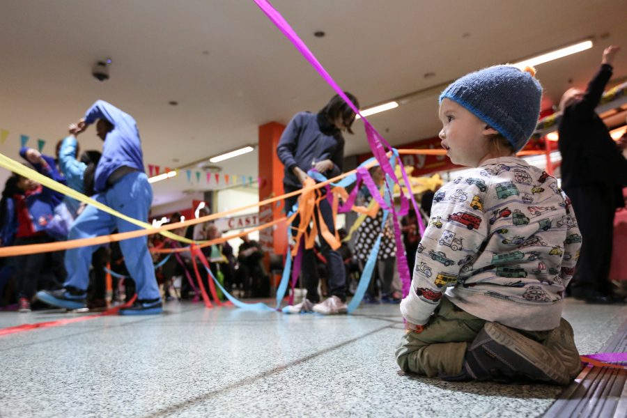 Young child on floor looking in awe at streamers