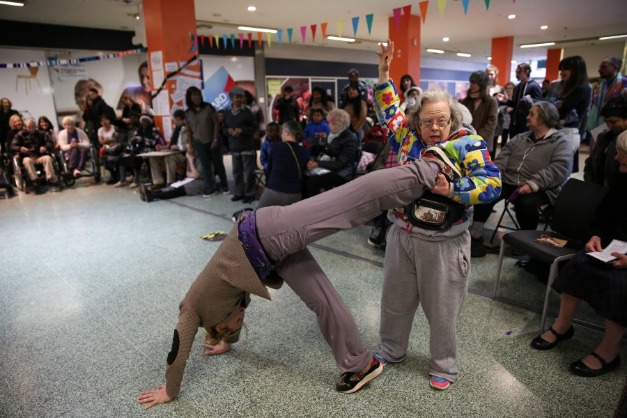 man doing handstand older woman holding leg up