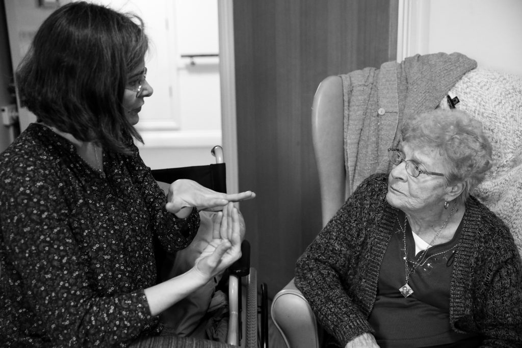 artist talking to older person in care home