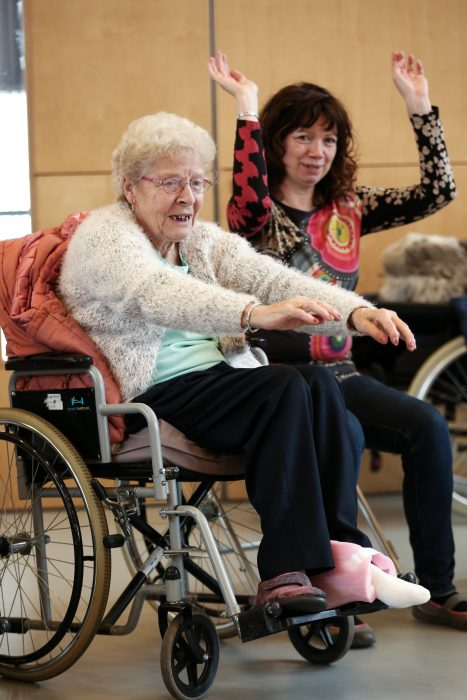 woman in wheelchair reaching arms out