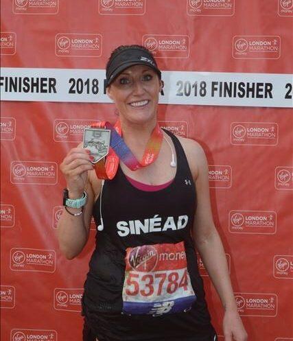 marathon runner holding medal