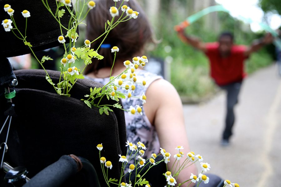 Woman in wheelchair with flowers and man dances in background