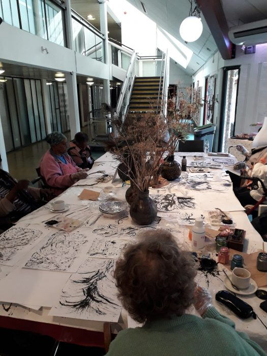 people painting around a table
