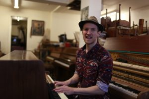 man playing piano in a hat