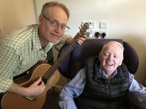 Man with guitar and man in chair smiling