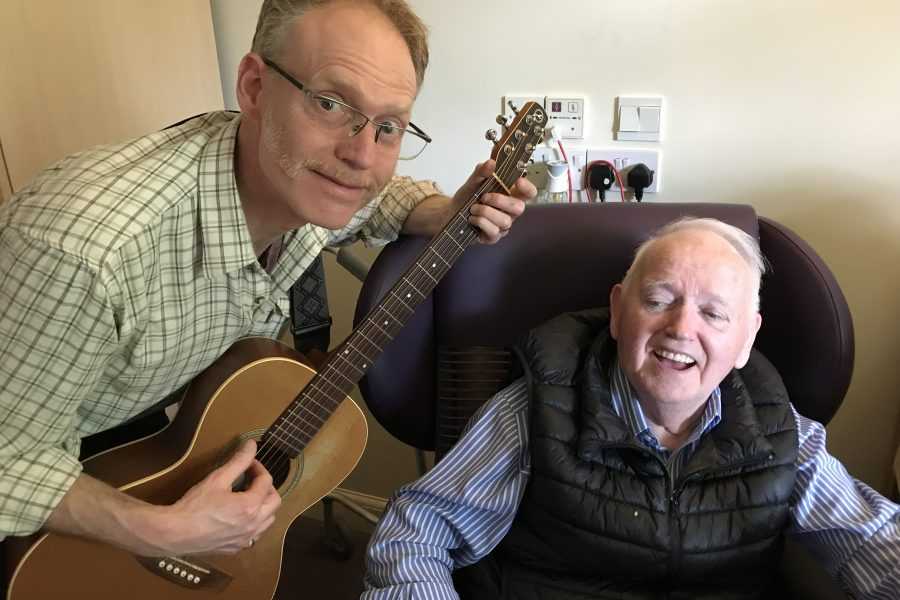 man playing guitar and older man in chair