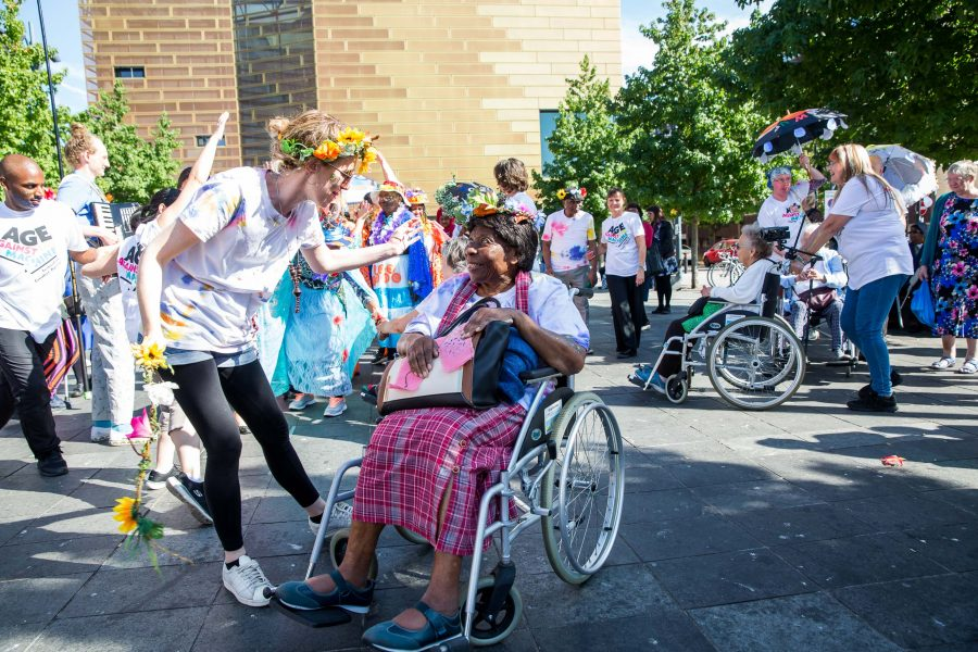 woman in wheelchair smiling and arm waving with a group of people