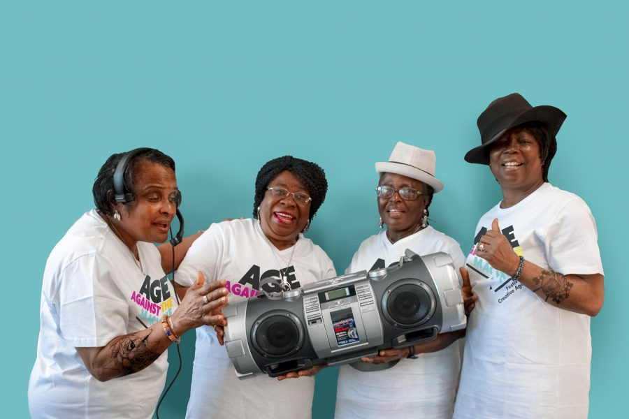 4 people smiling holding an old style ghetto blaster