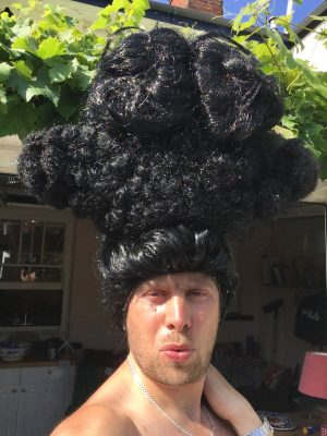 Man waering large black wig