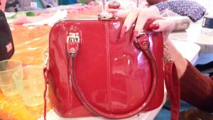 Red handbag with hand and red nails