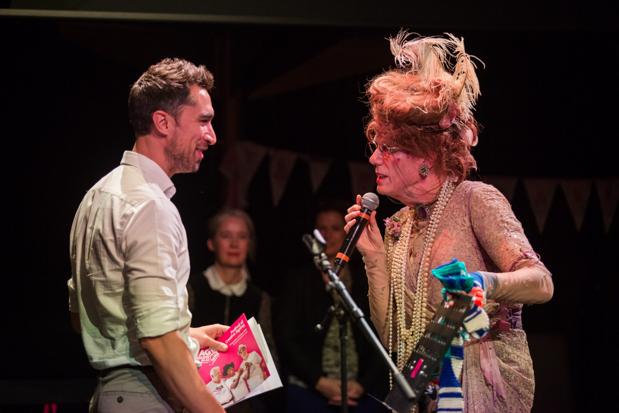 man dressed as woman talking to a man on stage