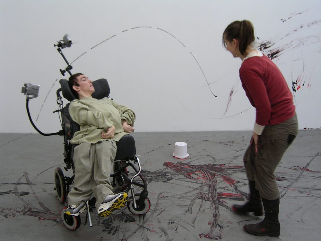 Girl in wheelchair and artist splashing paint around a room