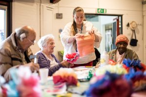 older people making paper flowers