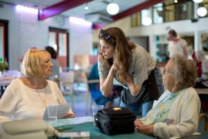 young woman talking to older women