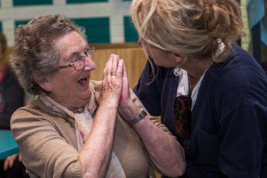 Older woman laughing with a carer