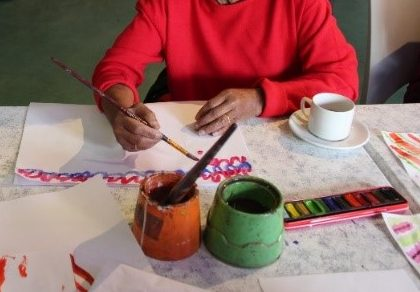 hands of elder person painting