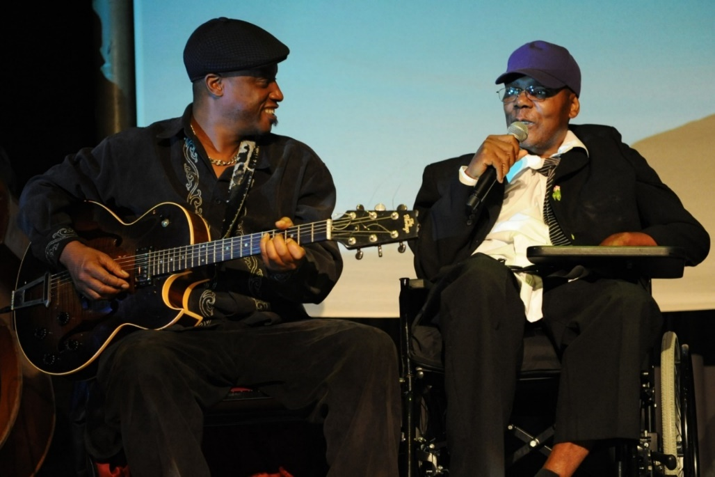 man in wheelchair with microphone and man with guitar smiling