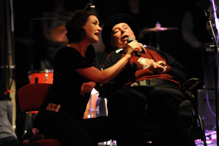 man in wheelchair singing into microphone held by a women