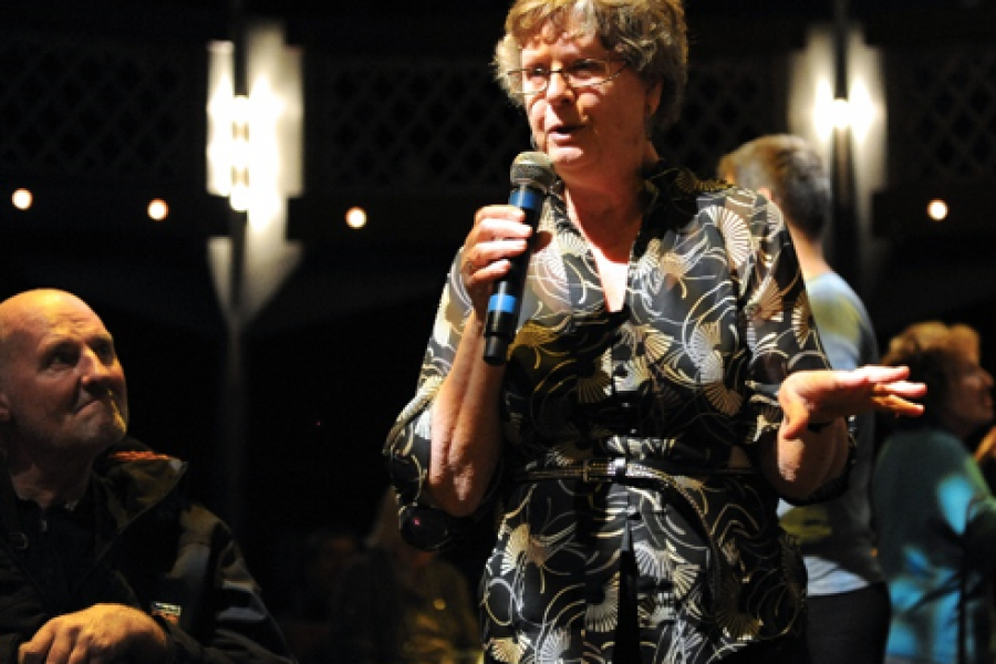 older woman holding microphone singing