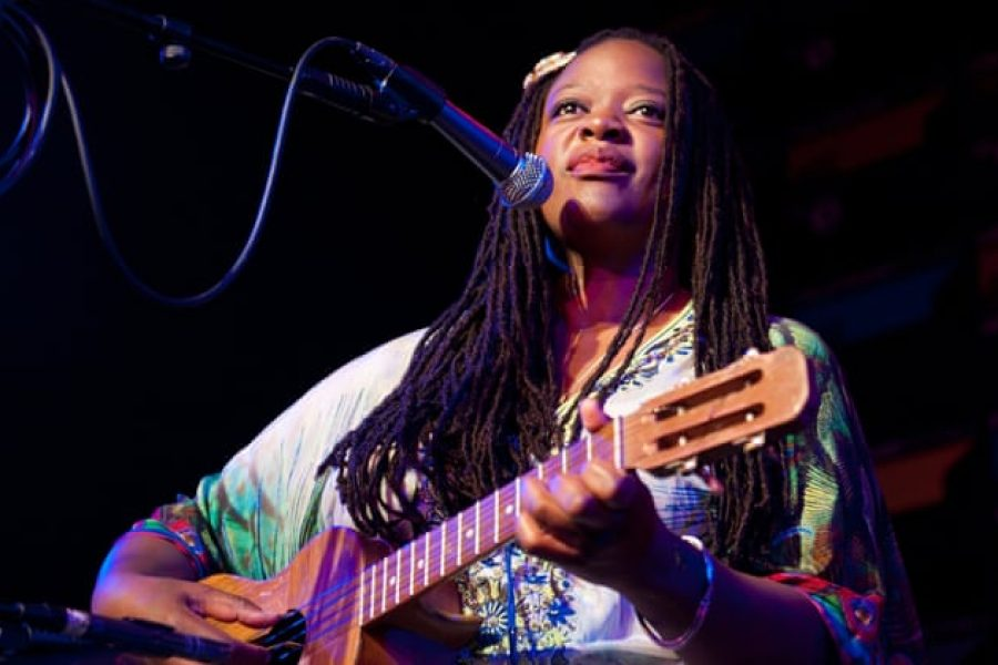 black african woman with guitar singing on stage