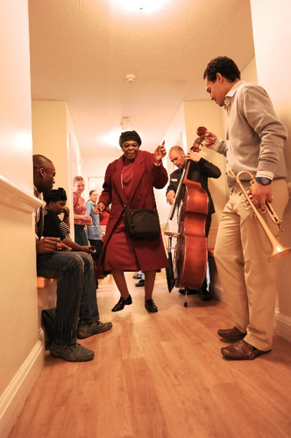 women dancing in care home corridor with a group of musicians