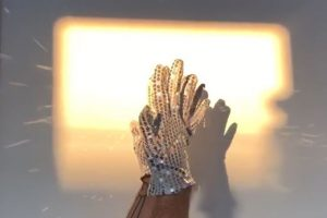 hands with glitter gloves in a square of light