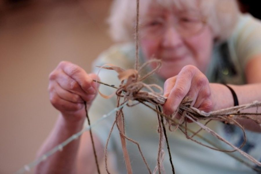 Older woman making a sculpture with string and sticks