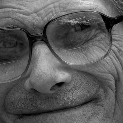 close up of a mans face with glasses, he is smiling