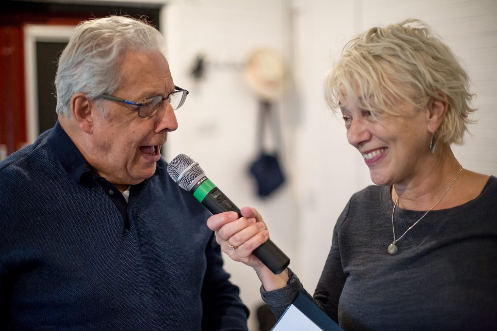 Woman holding a microphone with man talking