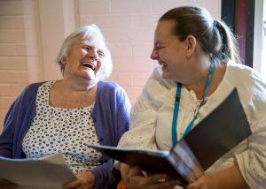 older woman and carer smilinga nd singing together