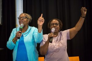two elder women singing with microphones arms raised smiling