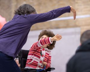 two people on in a wheelchair moving their arms