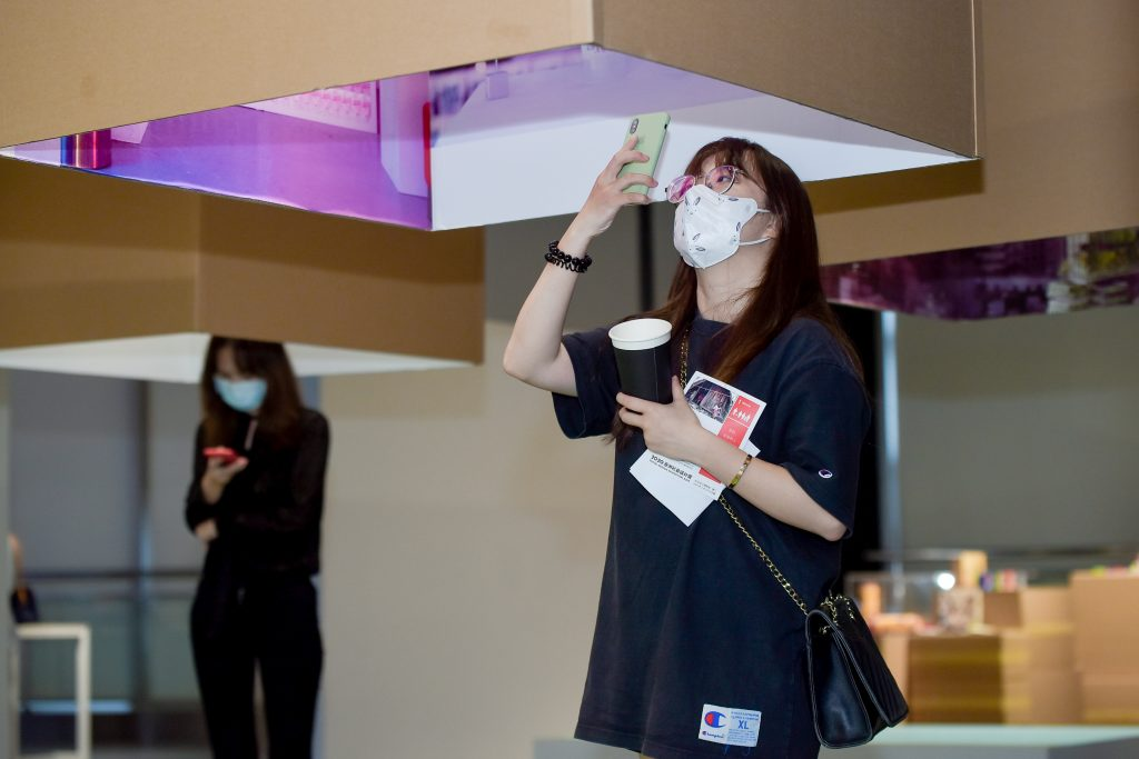 Chinese woman wearing facemask looking at an exhibition